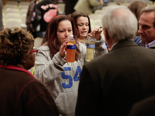 In this photo, taken in January, 2015, LeeAnne Walters 36 of Flint shows water samples from her home to Flint's new emergency manager Jerry Ambrose (before Darnell Earley was EM) after city an state officials spoke during a forum at Flint City Hall to discuss residents' growing health concerns about the drinking water.