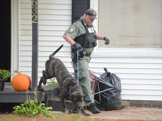 Battle Creek Animal Control Officer Mike Ehart removes Monster, a bull mastiff, from a home on Wellington Avenue last week.