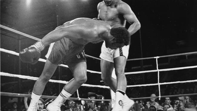 AP Muhammad Ali watches as George Foreman goes down to the canvas in the eighth round of their WBA/WBC championship match in Kinshasa, Zaire on Oct. 30, 1974. FILE - In this Oct. 30, 1974, file photo, challenger Muhammad Ali watches as defending world champion George Foreman goes down to the canvas in the eighth round of their WBA/WBC championship match in Kinshasa, Zaire. It was the Rumble in the Jungle and it's still a big part of the Ali lore today. Forty years have passed since the two men met in Africa to earn $5 million put up by dictator Mobutu Sese Seko, but time has done nothing to diminish its place in boxing history. (AP Photo/File)