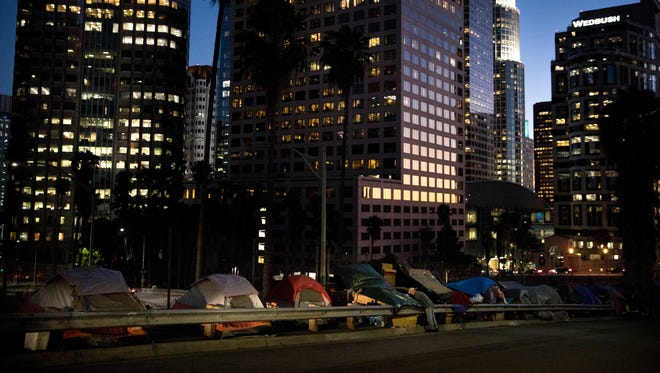 Homeless tents are dwarfed by skyscrapers as 63-year-old Vincent, who only gave his first name, sorts his belongings Friday, Dec. 1, 2017, in Los Angeles.