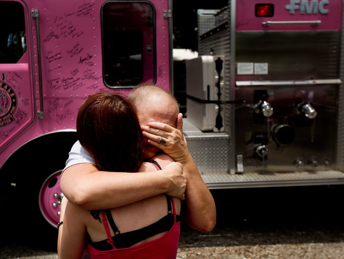 An emototional Dawn Louchart gets a hug from daughter, Cheyenne Louchart after the Pink Heals Southwest Florida Chapter fire truck payed a visit to her home on Wednesday 7/23/2014.  Louchart is battling stage three breast cancer. Fort Myers firefighters and Fort Myers Police along with volunteers accompanied the brigade to bring comfort and support to Louchart and her family.   The truck is used for anyone dealing with cancer.  Louchart received flowers and hugs along with support.  Louchart also got to sign the truck.