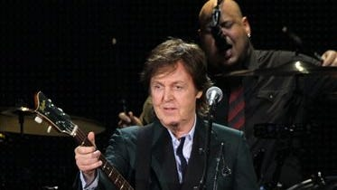 File- This July 9, 2013, file photo shows Paul McCartney performing at Fenway Park in Boston. McCartney is rescheduling U.S. tour dates as he continues to recover from a virus he received treatment for last month. The former Beatles singer announced Monday, June 9, 2014, tour stops scheduled for mid-June will be postponed to October. He was supposed to kick off the U.S. leg of his tour Saturday. Instead his first show will be July 5 in Albany, New York. (Photo by Marc Andrew Deley/Invision/AP, File)