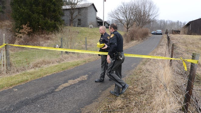Muskingum County Sheriff's Office deputies tape off the driveway to 5130 West Road near Adamsville after the bodies of a man and a woman were reported found in the home.