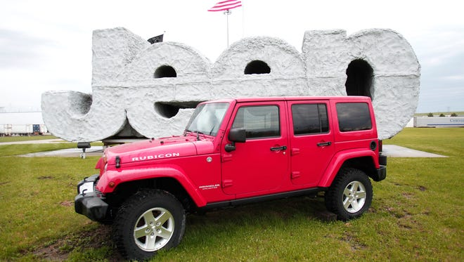 A 2014 Jeep Wrangler sits in front of a Jeep sign at the Chrysler Toledo North Assembly Plant where Jeep Wranglers and Cherokees are assembled.