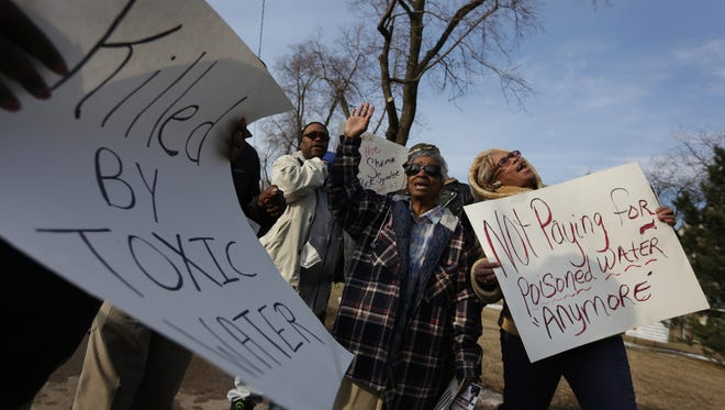 """""""We are tired and frustrated,"""" says Angela Hickmon of Flint, right during a rally where about 100 people demanded not to have to pay for water that has been tainted by lead in downtown Flint on Monday, January 25, 2016. """"The water is breaking me out. We are paying for something we can't use,"""" says Margie Scott, 71, of Flint, center. Romain Blanquart/ Detroit Free Press"""
