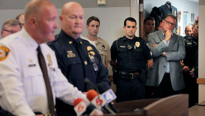 "Police officers listen as St. Louis County Police Chief Jon Belmar, left, and Ballwin Police Chief Kevin Scott speaks during a news conference, Friday, July 8, 2016 in Ballwin, Mo. A suburban St. Louis police officer was ""ambushed"" during a traffic stop Friday, injured critically after he was shot at least once from behind as he walked to his patrol car, authorities said."
