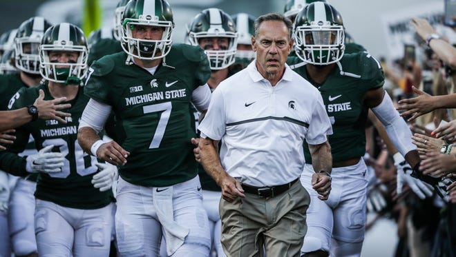 Michigan State team runs out of the tunnel to the field led by head coach Mark Dantonio before their home game opener against the Furman Paladins at Spartan Stadium in East Lansing, Michigan, on Friday, September 2, 2016.