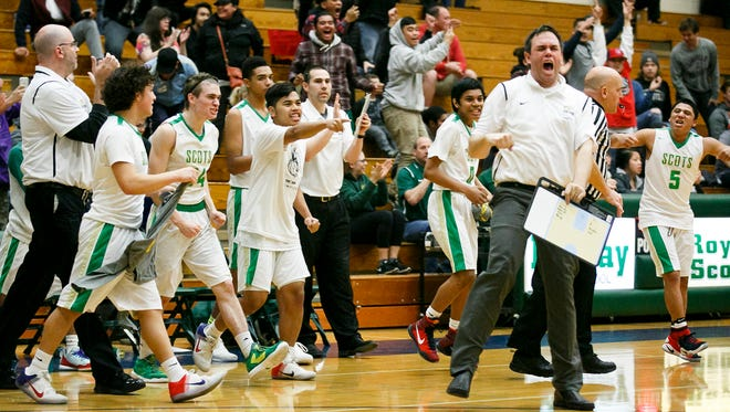 McKay basketball coach Dean Sanderson and players celebrate after a close 80-79 victory over McMinnville on Tuesday, Jan. 3, 2017, at McKay High School.