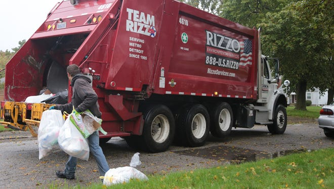 Rizzo Environmental Services workers pick up trash on Gold Ave. in Flint on Thursday, Oct. 27, 2016.