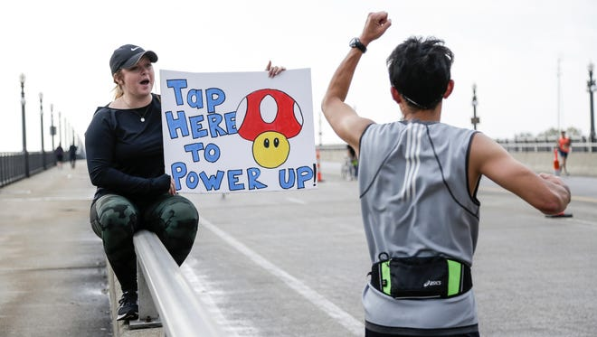 Danielle McNeilly, left, holds a Mario Brothers themed sign to cheer the runners on as they cross Belle Isle's MacArthur Bridge during the 40th Annual Detroit Free Press/Chemical Bank Marathon in Detroit on Sunday, Oct. 15, 2017.