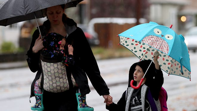 Rowan Fuller, 5, walks in the rain with his mom, Jessica Fuller, and sister Willow Fuller, 1, near Englewood Elementary in Salem on Thursday, Oct. 19, 2017.
