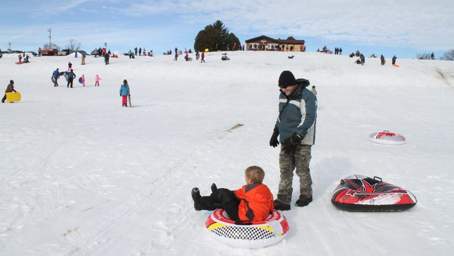 Luka Yakich, 10, and his dad Matthew finish a trip down the hill at Sussex Village Park in 2016. The village of Sussex will be hosting its annual Sledding Party at the park Saturday, Feb. 10.