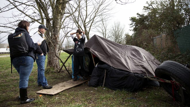 Clarissa, 28, right, answers survey questions from volunteers Carli Cohen and Jerry Steven during the Homeless Point-in-Time count outside her tent where she lives with her fiancee and four dogs along Highway 22 east of Lancaster Rd. SE in Salem on Wednesday, Jan. 31, 2018.