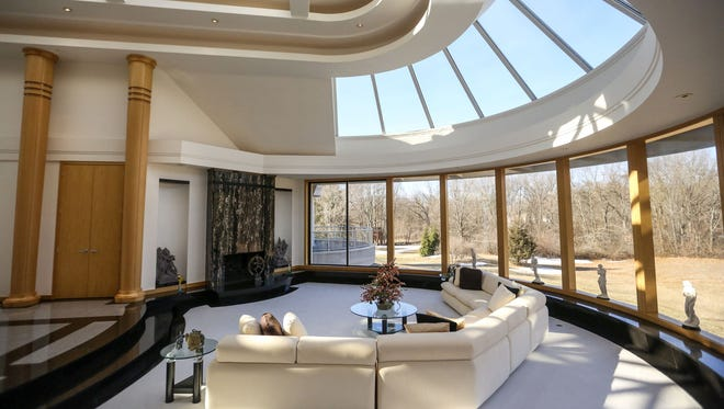 At the end of the long foyer, the wide, half-circle living room spreads out with a curved wall of windows under a curved ceiling of skylights.
