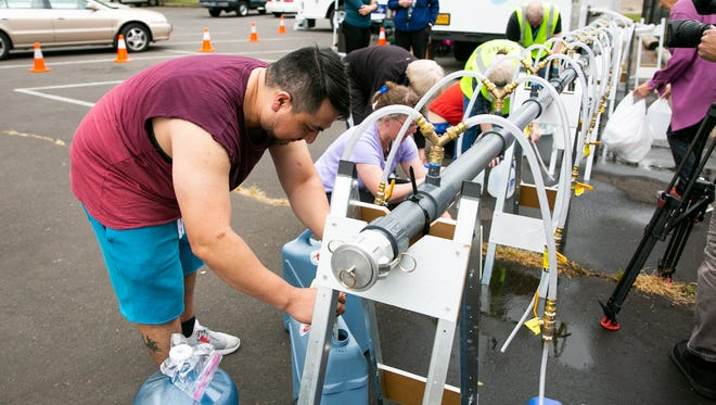 Erick Gonzalez and other Salem residents fill containers with clean water at a filling station run by the Keizer Community Emergency Response Team at the Keizer Civic Center on Thursday, May 31, 2018.