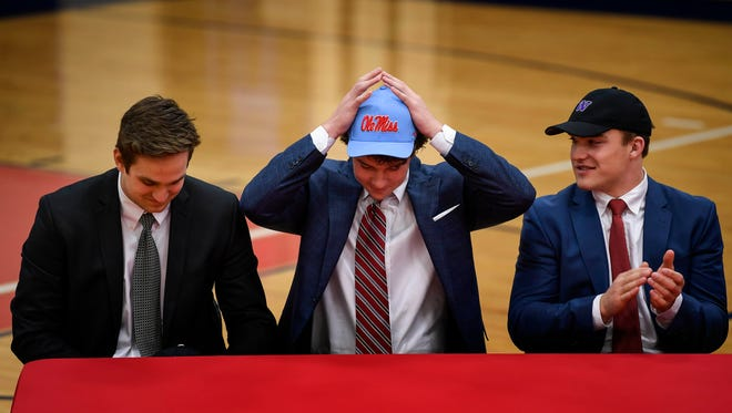 Football players Gavin Schoenwald, left, who signed with Vanderbilt, and Jackson Sirmon, right, who signed with Washington, watch as Luke Knox puts on an Ole Miss cap during a celebration Wednesday at Brentwood Academy.