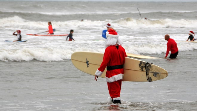 "George Trosset hosted the ""Surfin' Santas"" event in Cocoa Beach, Fla., on Dec. 24, 2013, with more than 200 surfing Santas, elves, snowmen and other Christmas characters decked out for the event. The annual event raised money for the non-profit Grind for Life."