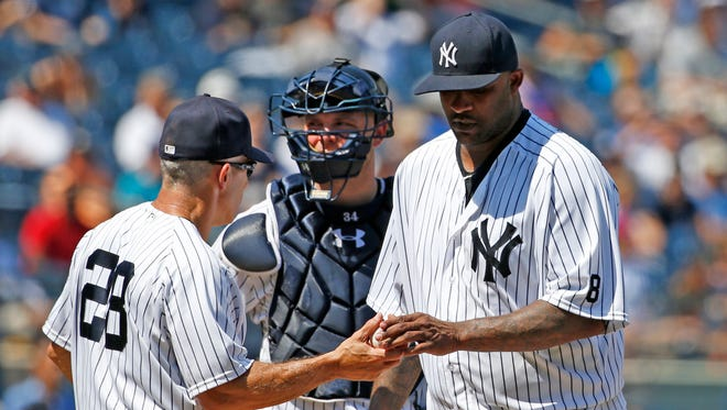 New York Yankees manager Joe Girardi (28) takes the ball from starting pitcher CC Sabathia after Sabathia allowed a two-run double to Baltimore Orioles Jonathan Schoop in the seventh inning of a baseball game in New York, Thursday, July 21, 2016. Yankees catcher Brian McCann, center, watches.