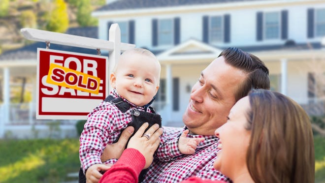 Young family standing in front of a SOLD sign on a front yard.