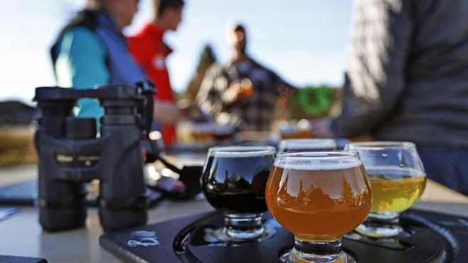 Birding enthusiasts discuss their day over a flight of beers at the Maine Beer Company in Freeport. The Maine Brew Bus tour group combines bird watching and craft beers into popular trips throughout southern Maine.