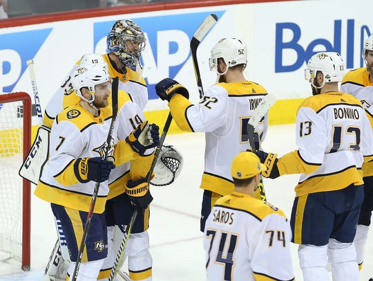 Teammates congratulate Pekka Rinne #35 of the Nashville