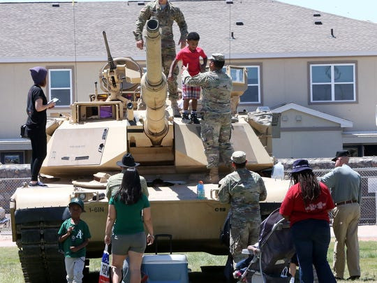 Children climb up on a M1A2 Abrams Battle Tank at the Armed Forces Day Open House at Biggs Park at Fort Bliss in May 2016.