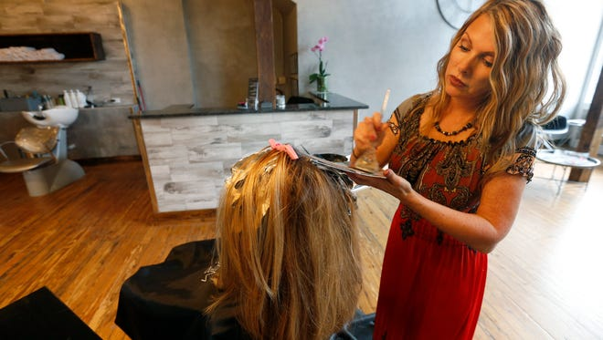 Robin Daniels colors a customers hair at Mane Salon & Social House at 404 W Walnut St.