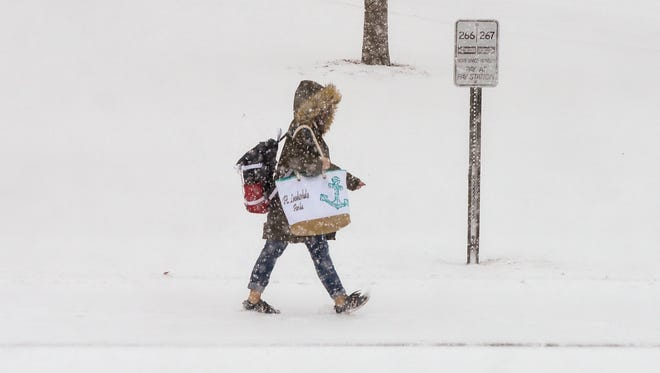 A pedestrian braves the heavy snow Saturday, April 14, walking across the campus of St. Cloud State University.