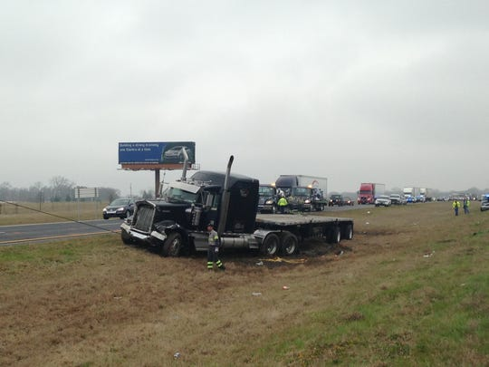 A tractor-trailer being pulled out of the median on Interstate 65.