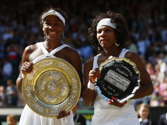 Venus, left, with the championship trophy and Serena