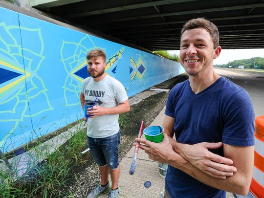Artist Matt Fitzpatrick (left) an art teacher at Newburgh's Castle High School and Jon Whitman a graphic designer at Shoe Carnival work on a 9 feet tall and 75 feet wide mural under the I-69 and U.S. 41 overpass recently. The mural, designed by Whitman, features Indiana's state seal, the peony as the state flower and the cardinal the state bird on July 28.
