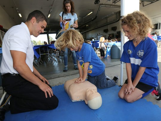 Ventura College EMT student Jose Perez, from left, watches as Kaikoa Leiner administers CPR to a mannequin as his sister Calia Leiner looks Saturday at Ventura County Fire Station No. 41 in Simi Valley Saturday. The fire department was also promoting a smart phone app called PulsePoint.