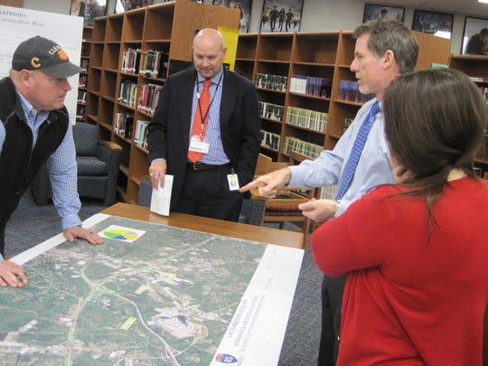 South Carolina Department of Transportation project engineer Kevin Sheppard, second from left, points to potential traffic problems on I-85 interchanges in northern Anderson County during a public input meeting Tuesday in Powdersville..