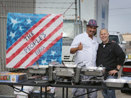 """Oxnard chef Victor Ortiz, left, gives a thumbs up with his friend Jarrod Chambers during the first """"People's BBQ"""" Monday at the Community Action of Ventura County's facility in Oxnard. Ortiz is the driving force behind the event, which fed between 150 to 200 homeless people  live in Oxnard."""