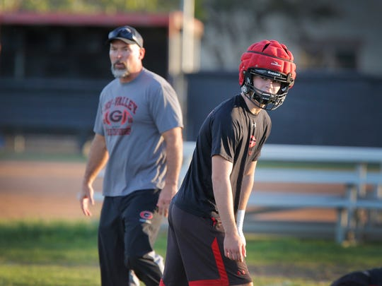 Grace Brethren running back/linebacker Joshua Henderson gets set to run a play as his father and the Lancers head coach Josh Henderson watches during a practice.