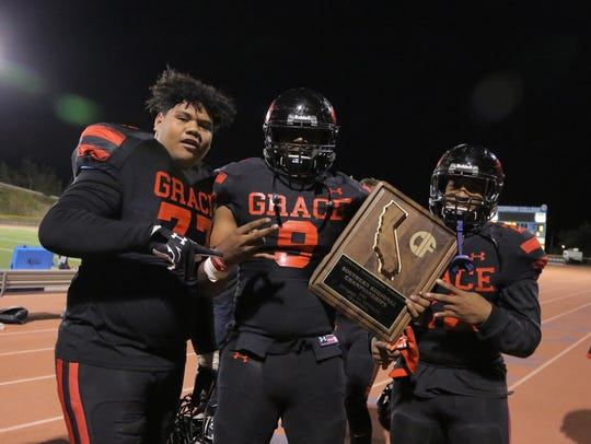 Grace Brethren's David Toia, left to right, Jordan Banks and Lontrelle Diggs hold up the plaque after the Lancers won the CIF-State SoCal Regional Division 2AA championship game last season. Diggs, a powerful running back, is one of the top returning players in the county.