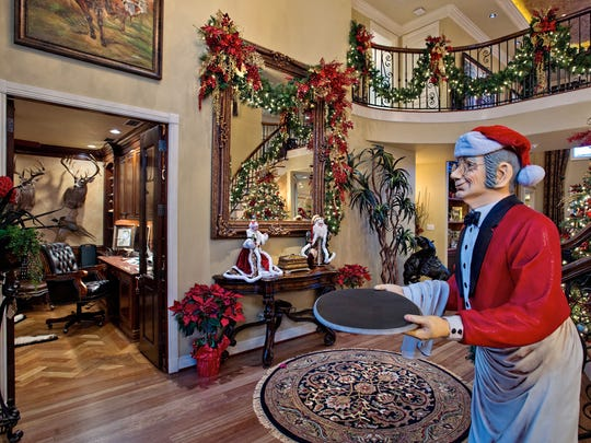 A cool butler statue beside a winding staircase greets visitors into the home's gorgeous entry which is beautifully decorated for the holiday season