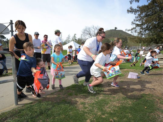 Kids and their parents make a dash in search of Easter eggs during a 2018 Easter egg hunt.