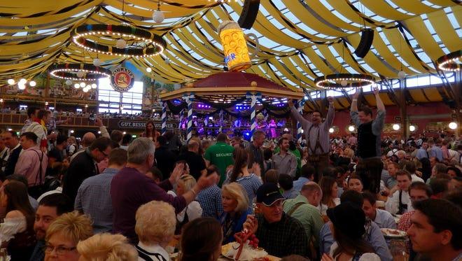 Thousands of people celebrate Oktoberfest in giant beer halls.