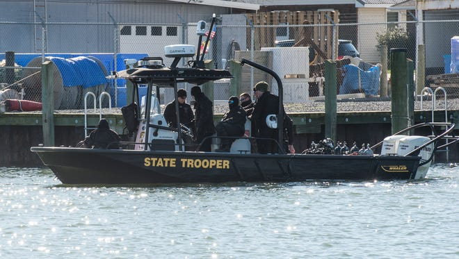 Maryland State Police officers make their way to the Atlantic Ocean to investigate a plane crash on Thursday, March 8, 2018.