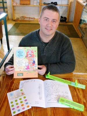 """Michael Ball Jr. displays the """"Watch Me Grow"""" children's milestone booklet kit and Footer foot-measuring tool manufactured by Woodrow Engineering in Sister Bay. The two products are being marketed as a kit, and Ball is seeking a FedEx grant through an online vote."""