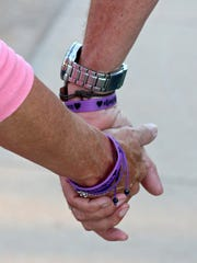 Bianka and Vern Landavazo walk home holding hands on Aug. 28 after visiting the memorial at the site of their daughter's murder.