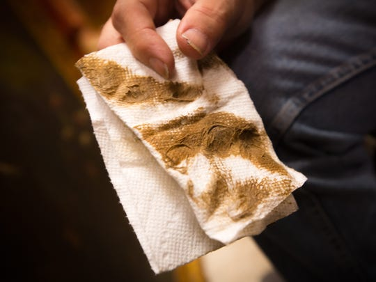 Art restorer Damon LaGarry holds up residue of cigarette smoke and other particulates he cleaned off of a painting under restoration at the Double Eagle restaurant.