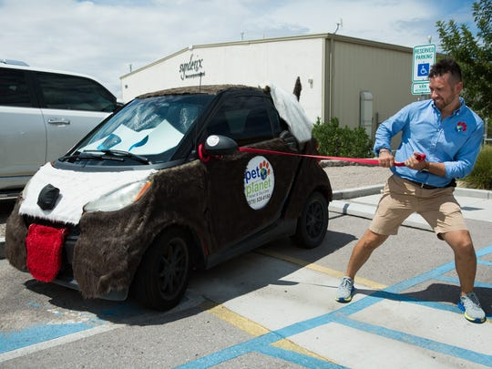 Pet Planet owner David Garcia pretends to walk the Pet Planet advertising vehicle, Wednesday, August 31, 2016. Garcia created the design and upholstered the vehicle himself. David and Juliana Garcia started a mobile pet grooming business in 2008 and later built Pet Planet Hotel and Day Camp at 971 Sand Castle Avenue.