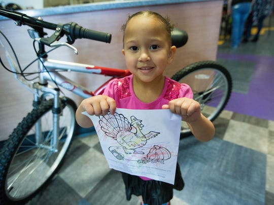 Kendra Phillips, 3, shows off her submission to a coloring contest at 10 Pin Alley, Thursday Nov. 23, 2017 at the bowling alley's Thanksgiving celebration for the community.