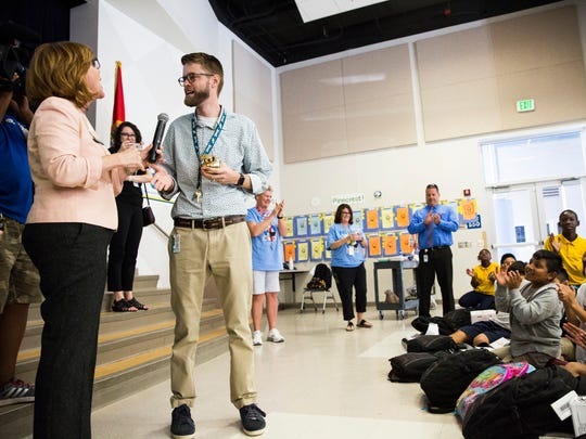 Dylan Opper, a fifth-grade teacher, accepts a Golden Apple award during a surprise presentation at Pinecrest Elementary in Immokalee on Friday, Feb. 23, 2018.