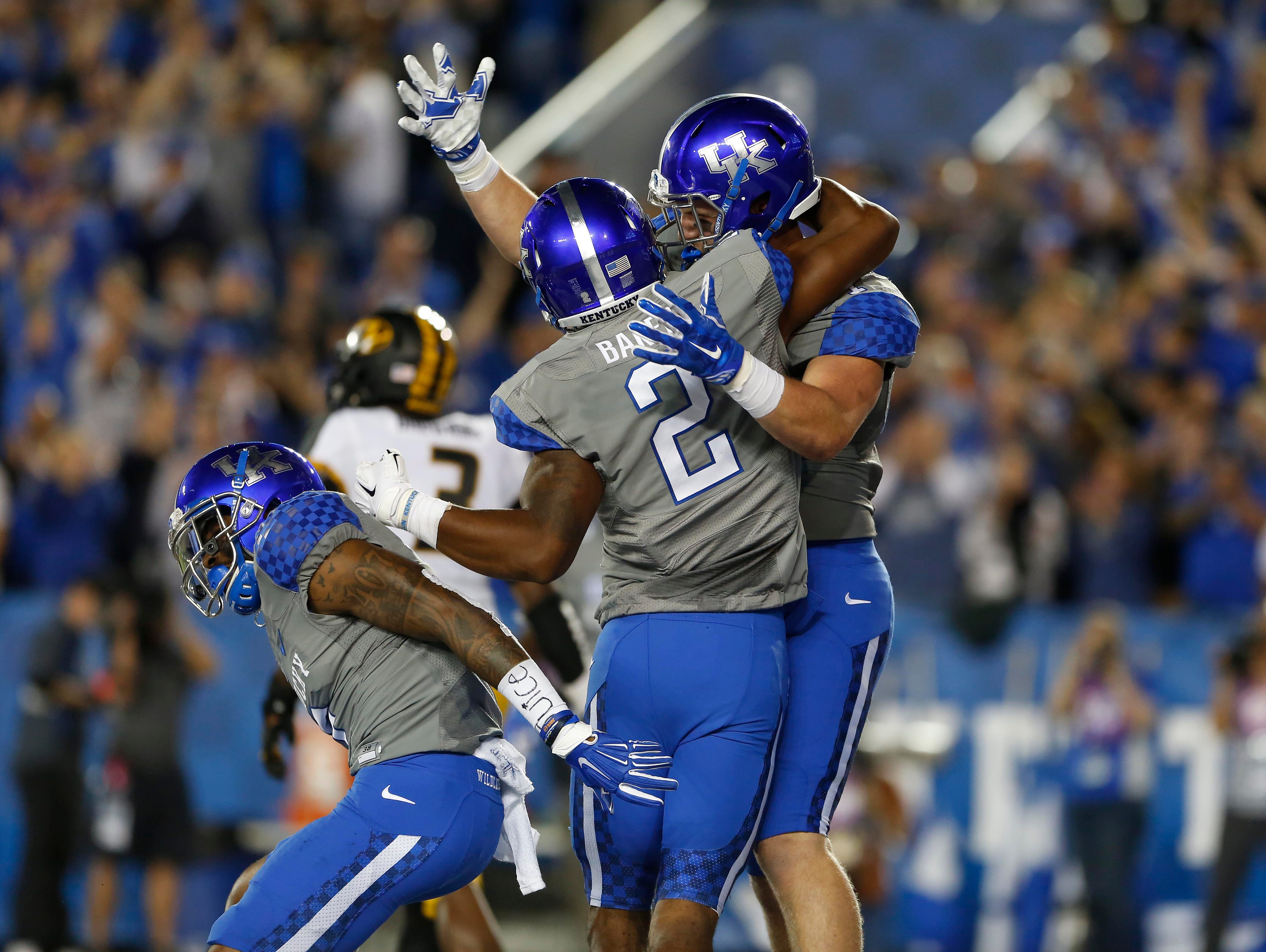 The Kentucky Wildcats' C. J. Conrad (87) celebrates with wide receiver Dorian Baker (2) after scoring a touchdown against the Missouri Tigers in the second half at Commonwealth Stadium. Kentucky defeated Missouri 21-13.