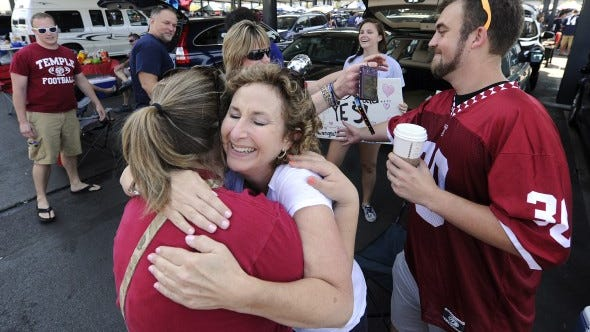 Noelle Duscha embraces her daughter Taylor during a celebration of her engagement to Temple graduate Dan Price, right,  in the parking lot before the start of the Penn State game against Temple in Philadelphia on Saturday, Sept. 5, 2015. Taylor's family are Penn State fans and her dad, Kevin, second from left, rear, graduated from Central York High School.    Jason Plotkin - York Daily Record/Sunday News