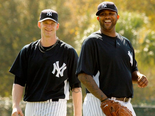 Yankees pitchers A.J. Burnett and CC Sabathia share a laugh during the first day of 2009 spring training in Tampa, Fla. While everyone else was saving their pennies, the Yankees were spending big. Defying the economic crisis, they forked over $423.5 million to sign Mark Teixeira, Sabathia and  Burnett for the first season at the new $1.5 billion Yankee Stadium.