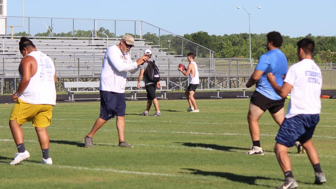 Stephenville High School varsity assistant football coach Jeremiah Butchee leads some Yellow Jackets through offseason workouts Thursday morning at Henderson Junior High School's Lem Brock Field.